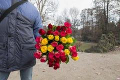 束玫瑰在手中在摊贩 谦逊的工作的例子,并且怎么得到居住在一个简单,但是诚实的方式 免版税库存图片