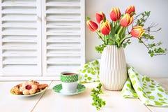 束红色郁金香、浓咖啡在绿色杯子有白色小点的和c 库存图片