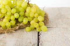 束绿色葡萄,秋天果子,丰盈的标志在土气木背景的与拷贝空间,顶视图,特写镜头 免版税库存图片