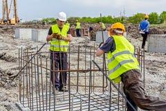 束缚钢筋为的建筑工人加强具体专栏 免版税图库摄影
