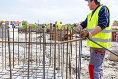 束缚钢筋为的建筑工人加强具体专栏 免版税库存图片