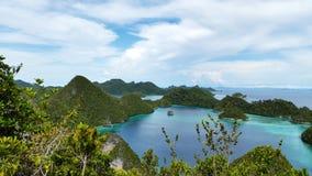 束美好的风景小山围拢了清楚的tosca水和明亮的蓝天和白色云彩,王侯Ampat 免版税库存图片