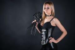 束腰的妇女有鞭子的 免版税库存图片