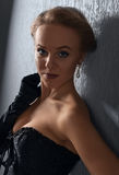 黑束腰的年轻美丽的妇女有珍珠耳环的 免版税库存照片