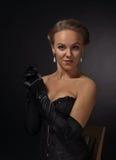 黑束腰的年轻美丽的妇女有珍珠耳环的 免版税图库摄影