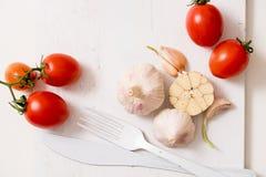 束蕃茄储蓄图象 在一个老木板条盘子的白色叉子刀子板材 艺术想法白色蕃茄,绘与油漆 B 库存图片