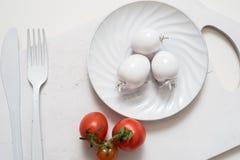 束蕃茄储蓄图象 在一个老木板条盘子的白色叉子刀子板材 艺术想法白色蕃茄,被绘 库存图片