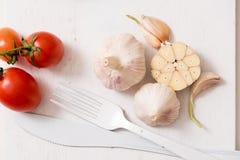 束蕃茄储蓄图象 在一个老木板条盘子的白色叉子刀子板材 艺术想法白色蕃茄,被绘 免版税图库摄影