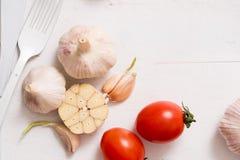 束蕃茄储蓄图象 在一个老木板条盘子的白色叉子刀子板材 艺术想法白色蕃茄,被绘 免版税库存图片