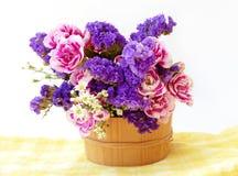 束起在木桶的桃红色和蓝色花 背景查出的白色 库存图片