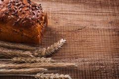 束起麦子耳朵面包在橡木木板的 免版税图库摄影