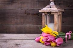 束起黄色和桃红色春天郁金香和蜡烛在灯笼在v 库存图片