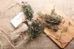 束麝香草、麻线和切板在粗麻布背景 库存图片