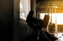 杠铃和哑铃集合在健身房,设备重量训练在机架,黑暗的被定调子的关闭的图片  免版税库存图片