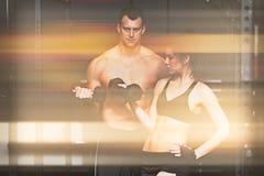 杠铃训练人和womanin健身房 库存照片