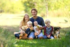 5条人和狗愉快的家庭在晴朗的庭院里 免版税库存照片