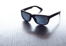 条纹的织地不很细表面上的黑太阳镜 库存图片