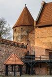 条顿人城堡和红砖在秋天季节的公园耸立 与一个倾斜的红砖屋顶的一座高塔在小山 免版税图库摄影