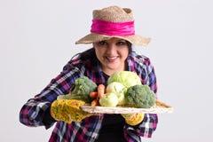 来克亨鸡的庭院妇女拿着一个盘子有很多菜 图库摄影