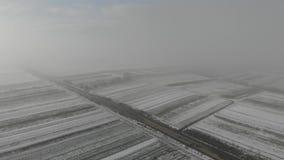 来冬天 领域鸟瞰图用雪和老公墓报道在路附近 股票录像