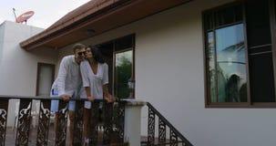 来到别墅议院阳台的夫妇看热带庭院、愉快的拥抱在夏天大阳台的男人和妇女 股票录像