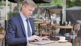 来和坐在咖啡馆大阳台的商人使用膝上型计算机 股票录像