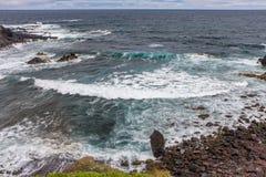 来岸上与大西洋的火山的石头波浪 免版税库存图片