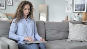 来,和开始工作的卷发妇女坐膝上型计算机