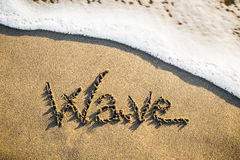 来临的波浪在沙子雕刻了 库存照片
