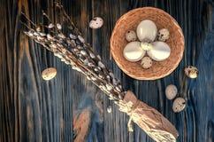 杨柳分支和鸡蛋在桌上 免版税库存照片