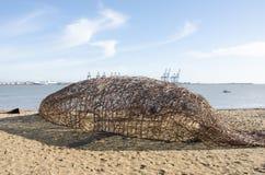 杨柳在海滩的鲸鱼雕象 库存图片