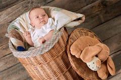 杨柳篮子的逗人喜爱的婴孩 图库摄影
