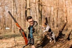 杨猎人的画象与一条狗的在森林 免版税库存照片