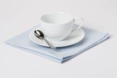 杯、板材和匙子在被折叠的方格花布棉花 免版税库存照片