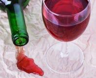杯与一个瓶的红葡萄酒在报纸 库存图片