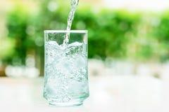 杯与一些水流量的凉水下来行动 免版税图库摄影