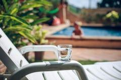 杯与下落的水由水池边在热带海滩胜地 库存照片
