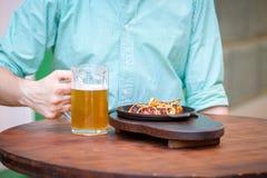 杯与与一块香肠板材的低度黄啤酒在一张黑暗的桌上 图库摄影
