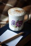 杯与书、空的纸和铅笔垂直的热奶咖啡 免版税库存照片