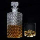 杯与冰和一个方形的蒸馏瓶的威士忌酒 免版税库存照片