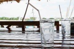 杯与冰和白色秸杆的纯净的水在木桌上 图库摄影