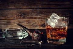 杯与冰和管子的威士忌酒在木背景 免版税图库摄影