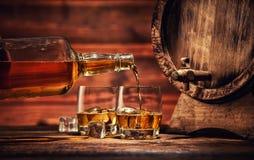杯与冰块的威士忌酒在木头服务 免版税库存图片