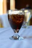 杯与冰块的苏打可乐在餐桌上 免版税库存图片