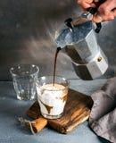 杯与冰淇凌的咖啡在土气木板 饮料从人的手举行的钢意大利人Moka罐倾吐 库存图片
