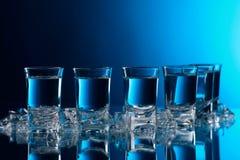 杯与冰的伏特加酒在玻璃桌上 免版税库存图片