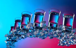 杯与冰的伏特加酒在玻璃桌上 免版税库存照片