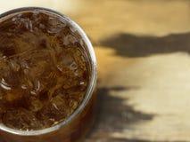 杯与冰的可乐在木桌上 库存照片