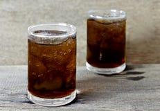 杯与冰的可乐在木桌上 免版税库存图片