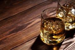 杯与冰的威士忌酒在木头 免版税库存照片